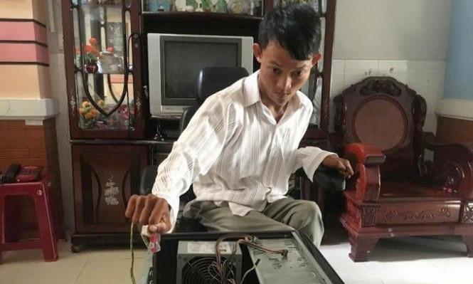 Ngọc Hiếu chăm chú sửa chữa máy tính cho khách hàng – Ảnh: NVCC