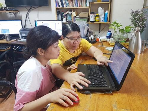 Chị Nguyễn Thị Mỹ Ngọc (phải) hướng dẫn nhân viên thao tác trên máy tính