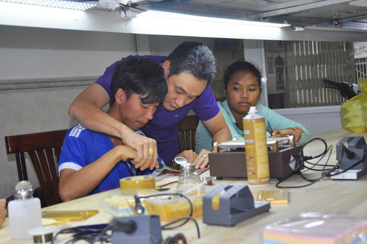 Anh Thịnh, chủ cửa hàng đang chỉ dạy cho học viên cách tháo lắp màn hình điện thoại di động