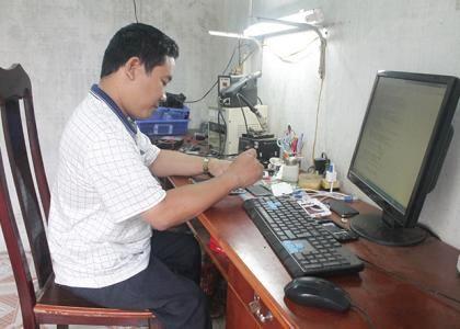 Anh Phạm Văn Nhân đang sửa chữa điện thoại ở cửa hàng của mình trên đường Lê Lợi (TP. Đồng Hới).